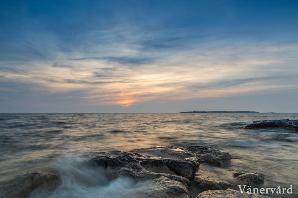 Vy från Raholmens laxhallar i solnedgång. Ön man ser till höger i bild är Timmeröarna.