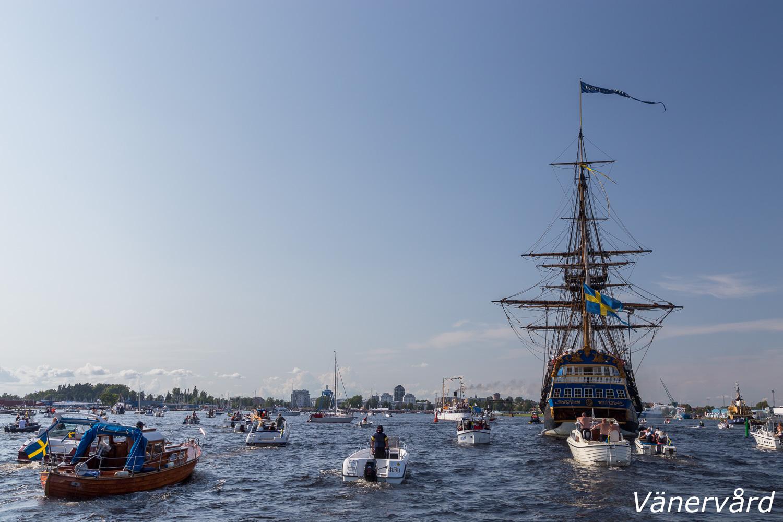 Ostindiefararen på väg in mot Wärmlandskajen med en mängd båtar som följe.